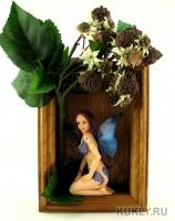 Волосы – коза.  Глаза авторские, ручной работы.  Ресницы -  натуральный мех.  Костюм несъемный. Выполнен из кусочков натурального шелка, задекорирован блестками. Крылья выполнены из Fimo Gel. По телу куклы идет роспись. Кукла размещена в раме (вынимается). Рама задекорирована искусственными цветами и плодами, Высота композиции – 25 см. Высота куклы – 15,5 см, 2016